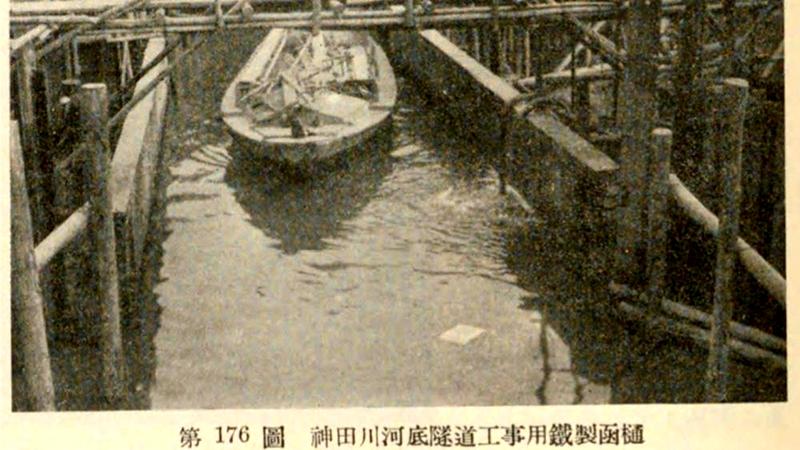 下图是正在建设下穿神田川的隧道之时,用铁制管道架起的神田川